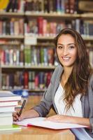 lächelnde brünette Studentin, die ihre Aufgabe erledigt foto