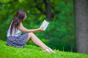 junges Mädchen, das ein Buch draußen im Park liest foto
