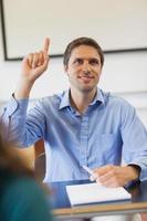 amüsierter männlicher reifer Student, der seine Hand hebt foto