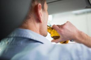 Mann trinkt Bier während der Fahrt