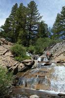 Frau sitzt an einem Wasserfall foto