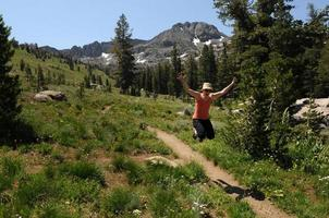 Frau springt über einen Wanderweg foto