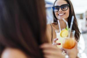 fröhliche Freundinnen, die Cocktails trinken foto
