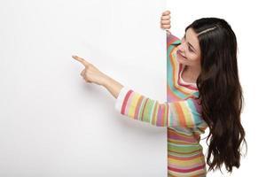glückliche lächelnde junge Frau, die leeres Schild zeigt. foto