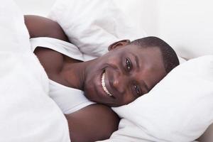 afrikanischer Mann, der auf Bett liegt