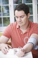 Mann, der zu Hause den Blutdruck misst foto
