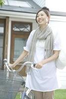 Frau schiebt Fahrrad foto