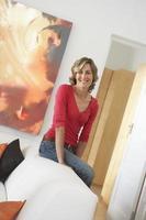 blonde Frau, die zu Hause auf Sessel stützt foto
