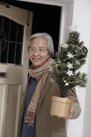 Mann kommt mit Baum nach Hause foto