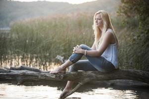 junge Frau, die auf Baumstamm am See sitzt foto