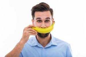 Mann hält Banane über Gesicht foto