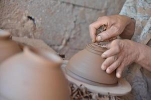 Der marokkanische Handwerker wirft einen Tontopf auf eine Töpferscheibe. foto