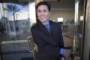 Geschäftsmann öffnet Tür, verlässt die Lobby des Gebäudes und lächelt foto