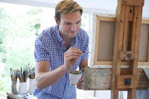 männliche Künstlermalerei im Atelier