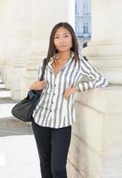 hübsche asiatische Frau, die steht und die Kamera schaut foto
