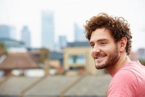 junger Mann mit Blick auf die Stadt von der Dachterrasse foto