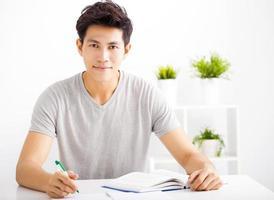 lächelnder entspannter junger Mann, der Buch im Wohnzimmer liest
