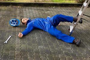 bewusstloser Techniker fiel von der Leiter auf der Straße foto