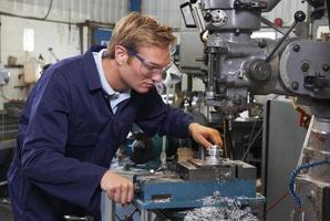Ingenieur mit Bohrer in der Fabrik foto