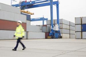 in voller Länge der Arbeiterin, die in der Schifffahrtswerft geht foto