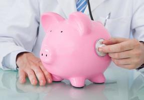 Arzt untersucht Sparschwein mit Stethoskop foto