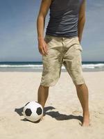 Mann, der Fußball am Strand spielt.