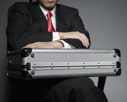 Geschäftsmann mit Aktentasche sitzt auf Stuhl foto