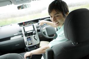 Mann, der die Kamera vom Fahrersitz des Autos betrachtet