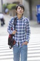 Mann mit Rucksackkreuzung am Kreuzweg foto