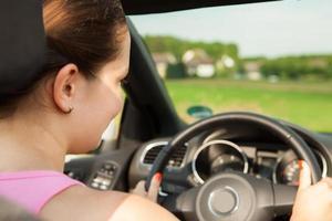 glückliche junge Frau, die das Auto fährt foto