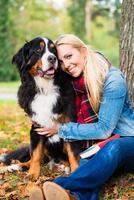 Frau, die mit Hund draußen im Park kuschelt foto