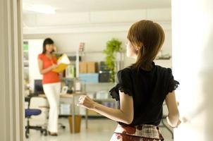 zwei junge japanische Frauen, die im Büro arbeiten foto