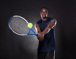 junger afrikanischer Mann, der Tennis spielt foto