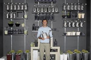 Mann, der neben Kakteenanzeige steht und Gießkanne hält