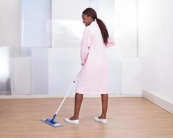 Haushälterin wischt Boden im Hotel foto