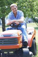 Mann schneidet Gras mit sitzen auf Mäher foto