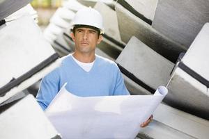 männlicher Architekt mit Blaupause, die auf der Baustelle arbeitet
