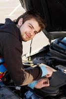 Autofahrer untersucht den Motor des Autos foto