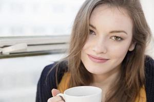 junge Frau hält eine Tasse Kaffee foto
