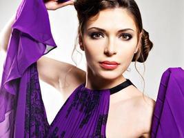Nahaufnahmegesicht der schönen Modefrau im lila Kleid foto