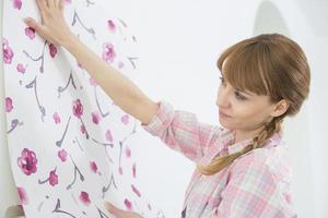 Frau, die Tapete an der Wand im neuen Haus anwendet