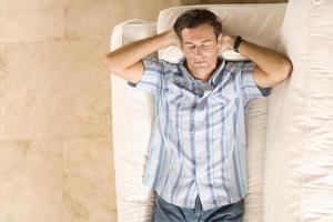 junger Mann schlafend auf Sofa, Hände hinter Kopf, erhöhte Sicht foto