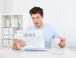junger Mann, der Zeitung liest foto