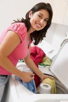 lächelnde Frau, die bunte Kleidung wäscht foto