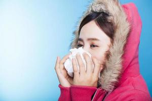 junge Frau putzt sich die Nase foto