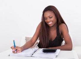 Frau, die Finanzen zu Hause berechnet foto