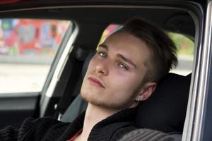 hübscher blonder junger Mann, der in seinem Auto sitzt foto