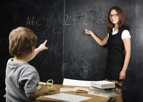kleiner süßer Junge im Klassenzimmer mit Lehrer foto