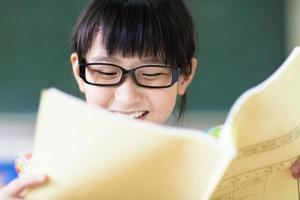 glückliches kleines Mädchen, das im Klassenzimmer studiert