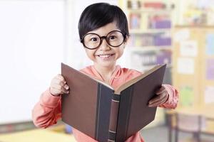 entzückendes Kind, das Lehrbuch im Klassenzimmer hält